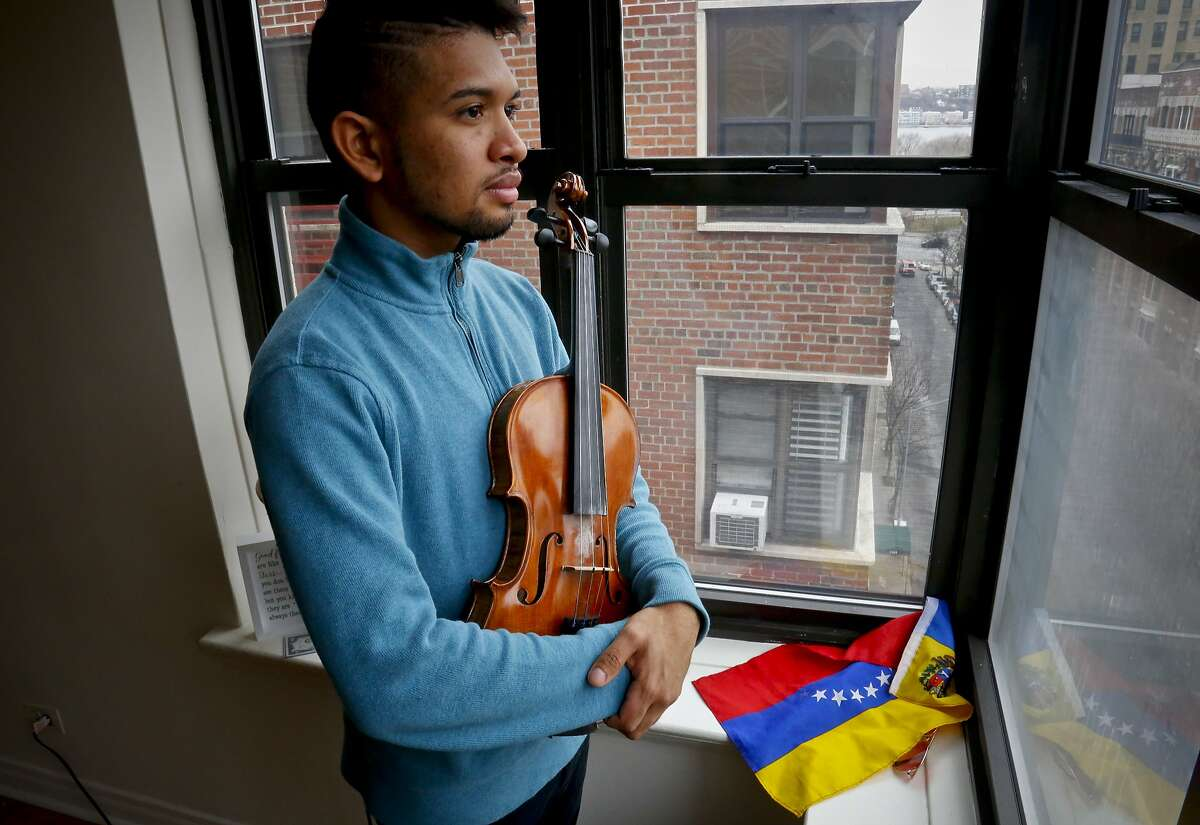 """In this March 28, 2018 photo, Venezuelan musician Wuilly Arteaga stands next to his country's flag holding his violin, as he pose during an interview in New York. """"I suffered a lot only because I played the violin against the government. I was tortured, I was put in jail,"""" said Arteaga. (AP Photo/Bebeto Matthews)"""