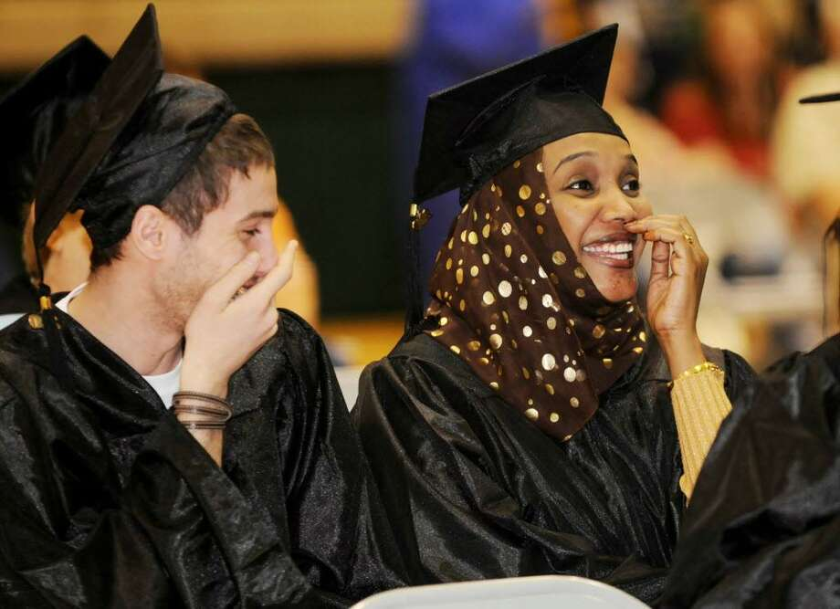 Adnan Aswad, left, and Thowaiba Fadul, both of Albany, share a laugh as they graduate Thursday from The Capital District Educational Opportunity Center. They each received a certificate in the English as a Second Language curriculum. Aswad is from Iraq and Fadul is from Sudan. ( Luanne M. Ferris / Times Union)