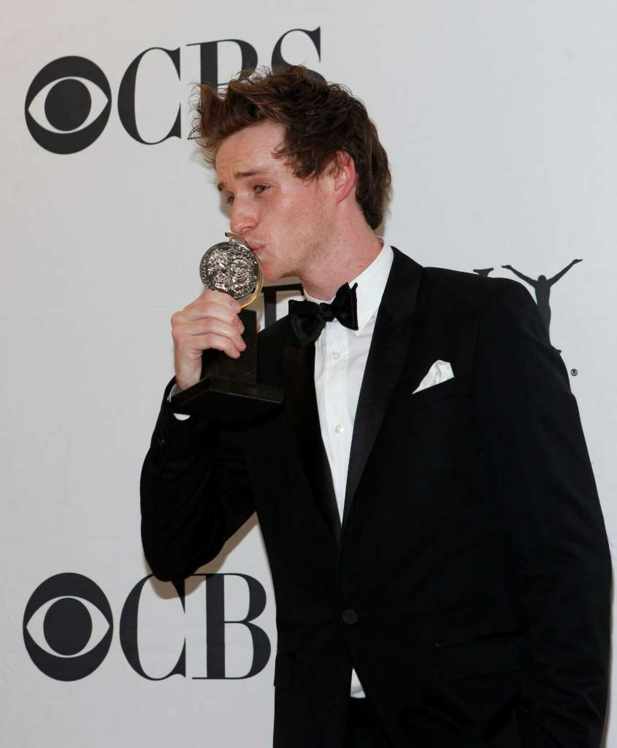 Eddie Redmayne kisses his Tony Award for Best Performance by a Featured Actor in a Play for