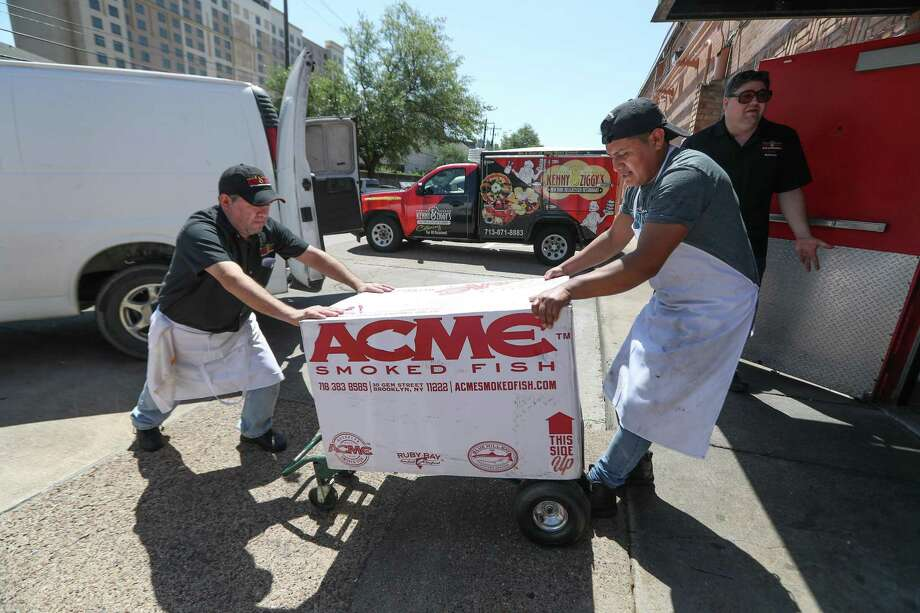 Kenny and Ziggy's employees Moses de la Torre (left) and Pedro Tzoy move a box of smoked fishes  chef/owner Ziggy Gruber (background) holds the door at his restaurant Wednesday, April 4, 2018, in Houston. ( Steve Gonzales / Houston Chronicle ) Photo: Steve Gonzales, Houston Chronicle / Houston Chronicle / © 2018 Houston Chronicle