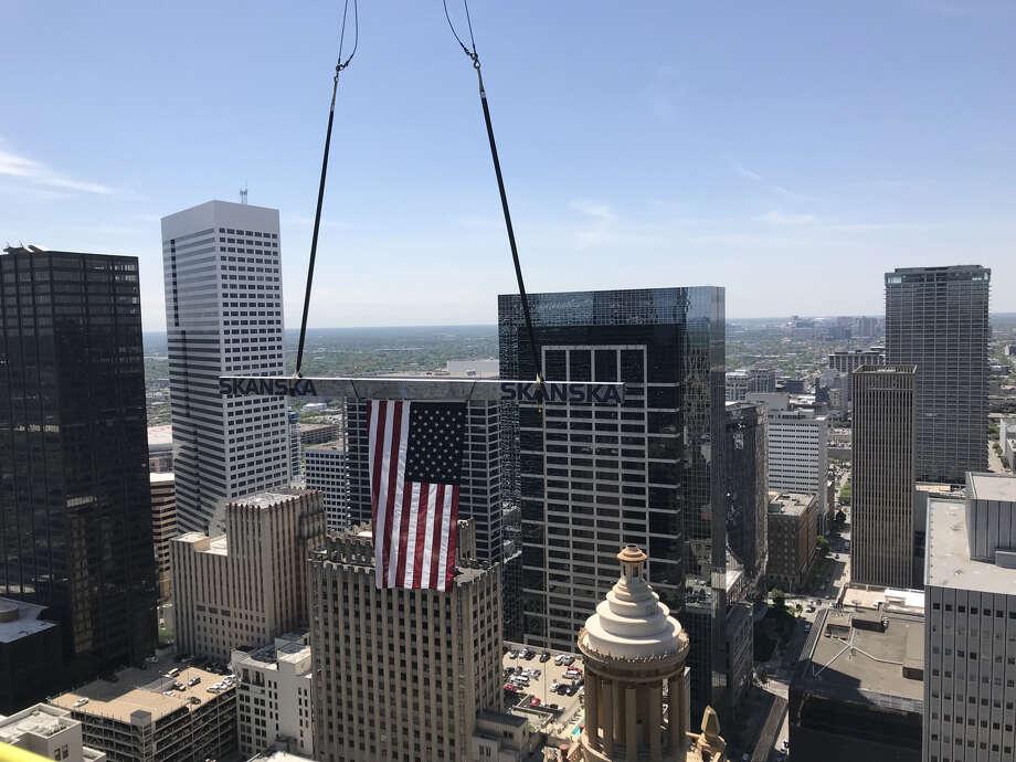 The beam and flag raised above Downtown Houston. Photo: Courtesy Of Skanska