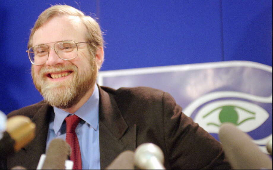 With the eye of the team logo peering over his shoulder, Microsoft co-founder Paul Allen laughs during a news conference at Seattle Seahawk headquarters Tuesday, April 23, 1996 in Kirkland, Wash. Allen says he purchased an option to buy the team to keep the Seahawks in Seattle. Photo: ELAINE THOMPSON/Associated Press, PI FILE