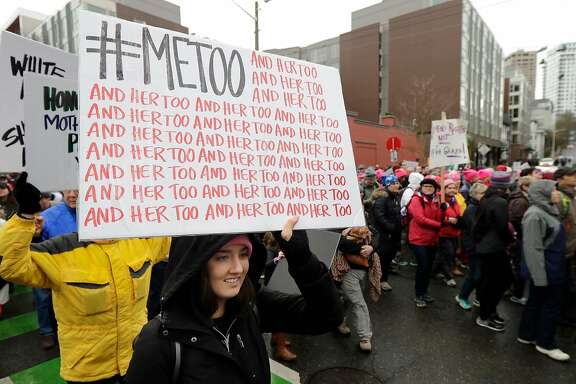 FILE - In this Saturday, Jan. 20, 2018 file photo, a marcher carries a sign with the popular Twitter hashtag #MeToo used by people speaking out against sexual harassment as she takes part in a Women's March in Seattle, on the anniversary of President Donald Trump's inauguration. Six months after bursting into the spotlight, the #MeToo movement has toppled scores of men from prominent positions and fueled a national conversation about workplace sexual harassment. Questions abound about the movement's staying power, but there's ample evidence that its impact will be durable. (AP Photo/Ted S. Warren)