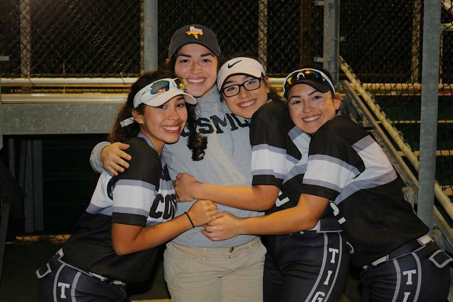 Former Conroe softball player Samantha Dawson, second from left, surprised her sisters Emily and Miranda Sanchez and cousin Isabel Perales by throwing out the first pitch at a home game recently after returning from the Marines. Submitted photo