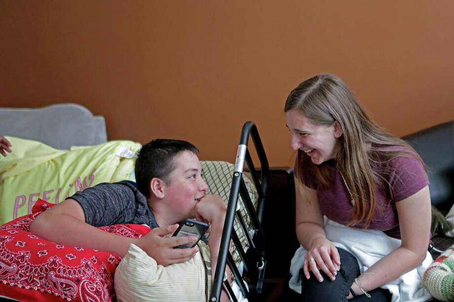 Kyle Laman, chattingwith friend Kellie Wanamaker at his home in Coral Springs, Fla., briefly rejoined classmates at Marjory Stoneman Douglas High School this week. Laman has undergone multiple surgeries to his foot because of a gunshot wound he received during the Feb. 14 massacre. Photo: John McCall, MBR / Sun Sentinel / Sun Sentinel