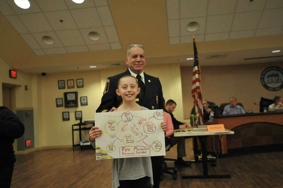 Torrington students were celebrated at Wednesday's meeting of the Board of Public Safety for winning the annual Fire Prevention Poster contest. Above, Torringford fourth-grader Julia Strager and Fire Marshal Ed Bascetta. Photo: Ben Lambert / Hearst Connecticut Media /