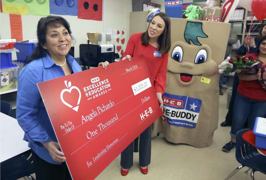 Bob Hope Elementary School teacher Angela Pichardo, left, holds a ceremonial check Thursday, April 5, 2018 with HEB public affairs employee Lauren Olson as Pichardo is honored with $1,000 for herself and a matching contribution to her school as part of HEB's Excellence in Education awards. Pichardo is now a finalist for the annual award which will be announced next month. Photo: William Luther, Staff / San Antonio Express-News / © 2018 San Antonio Express-News