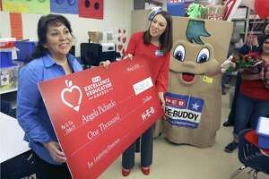 Bob Hope Elementary School teacher Angela Pichardo, left, holds a ceremonial check Thursday, April 5, 2018 with HEB public affairs employee Lauren Olson as Pichardo is honored with $1,000 for herself and a matching contribution to her school as part of HEB's Excellence in Education awards. Pichardo is now a finalist for the annual award which will be announced next month.