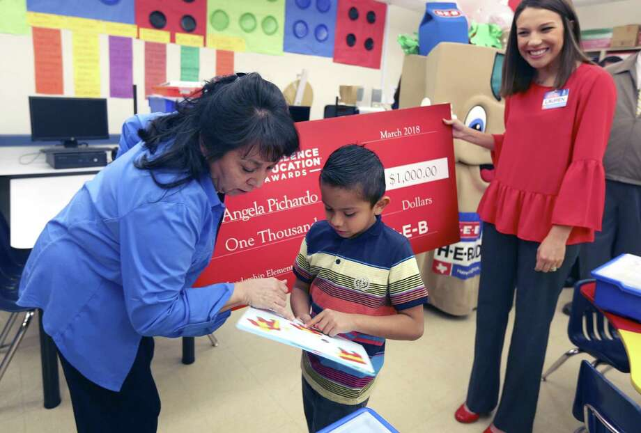 Unfazed by the throng of visitors to his classroom, Bob Hope Elementary School student Jacob Nolaceo asks teacher Angela Pichardo, left, a question about his classwork as she holds a ceremonial check April 5 with HEB public affairs employee Lauren Olson. Improving schools is the goal of a Trinity University School Design Network. Photo: William Luther /San Antonio Express-News / © 2018 San Antonio Express-News