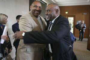 Outgoing board member Derrick Howard (left) and Willis Mackey embrace after Mackey was confirmed to the CPS Energy board Thursday. His confirmation by City Council was not unanimous, with three council members pointing out the lack of women on the board.