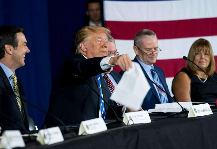 President Donald Trump tosses his prepared remarks into the air as he participates in a roundtable discussion on tax reform in White Sulphur Springs, West Virginia, April 5, 2018. (Doug Mills/The New York Times)