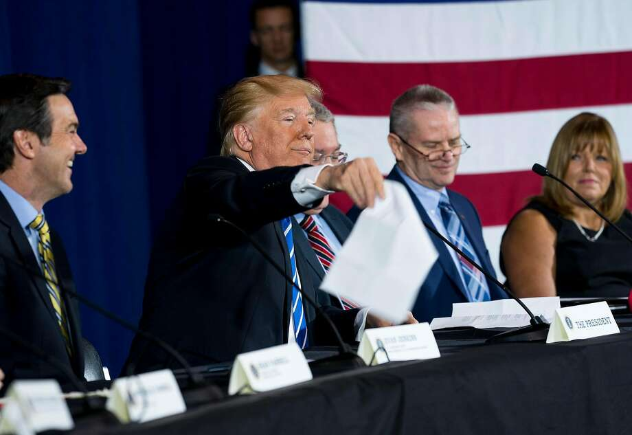 President Donald Trump tosses his prepared remarks into the air as he participates in a roundtable discussion on tax reform in White Sulphur Springs, West Virginia on April 5, 2018. Photo: DOUG MILLS, NYT