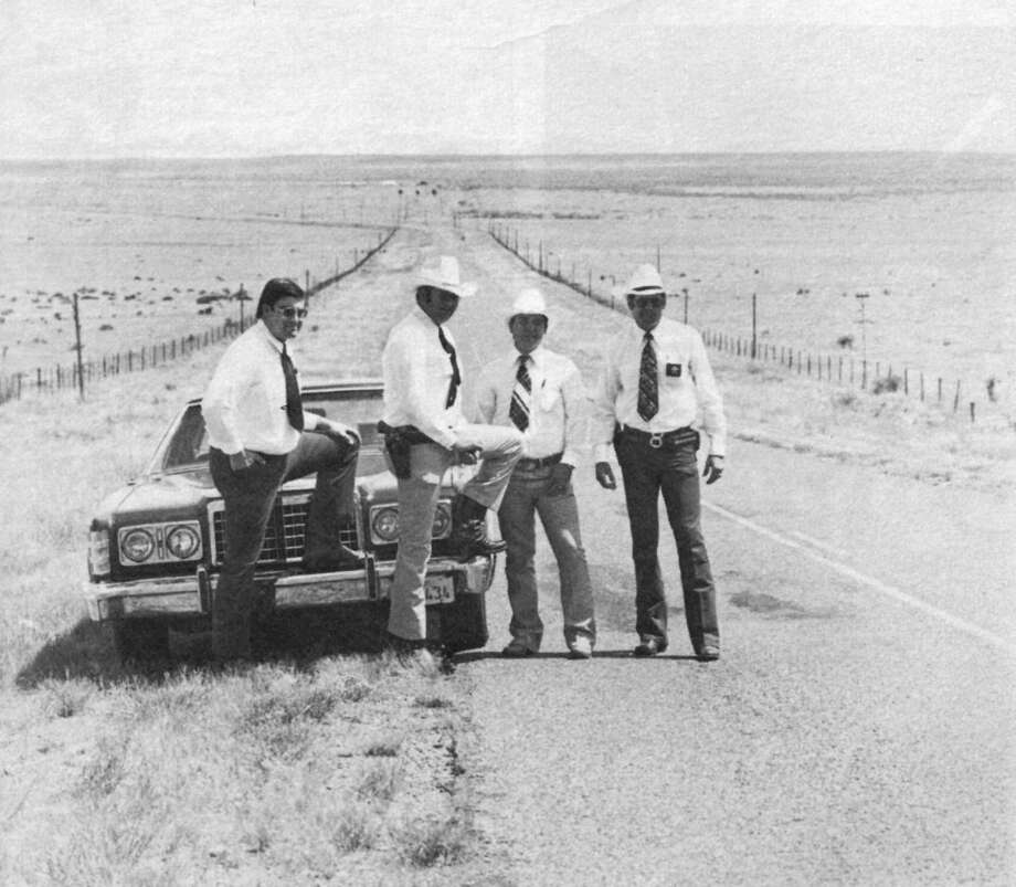 In 1977, on a highway south of Marfa, Presidio County Sheriff Rick Thompson, far right, posed for Texas Monthly with his crew (left to right) Jailer Robert Guevara, Deputy Gary Painter, and Deputy Roger Brito. Photo: Courtesy;John Bintliff, John Bintliff