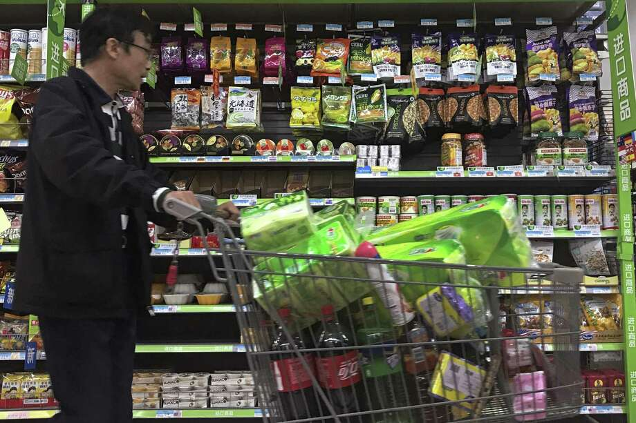 A man pushes a shopping cart past a display of nuts imported from the United States and other countries at a supermarket in Beijing, Monday, April 2, 2018.  China raised import duties on a $3 billion list of U.S. pork, fruit and other products Monday in an escalating tariff dispute with President Donald Trump that companies worry might depress global commerce. (AP Photo/Andy Wong) Photo: Andy Wong, STF / Associated Press / Copyright 2018 The Associated Press. All rights reserved.