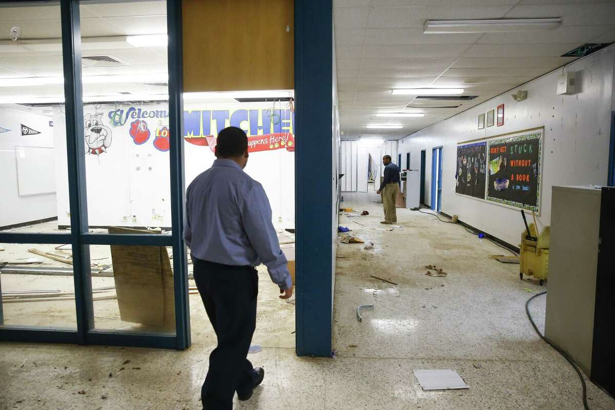 HISD security maintenance manager Rick Villanueva, left, and HISD Bond senior construction manager Sizwe Lewis, right, tour Mitchell Elementary Thursday, Dec. 14, 2017 in Houston. The school was flooded with about two feet of water during Hurricane Harvey. ( Michael Ciaglo / Houston Chronicle)