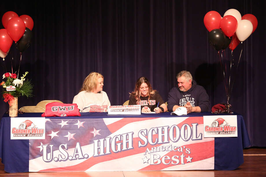 USA's Lauren Adam is joined by her parents Stephanie Long and Mark Adam, as she signs her National Letter of Intent to continue her basketball career at Gardner-Webb University, Tuesday, at USA High School. (Paul P. Adams/Huron Daily Tribune)