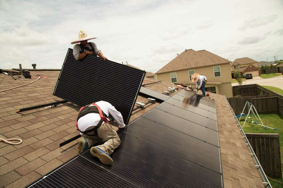 Workers from Alba Solar install solar panels on a home on Upland Sprint Terrace, Katy Texas, June 21, 2017. ( David A. Funchess / Houston Chronicle ) Photo: David A. Funchess, HC Staff Intern / David A. Funchess / Houston Chronicle