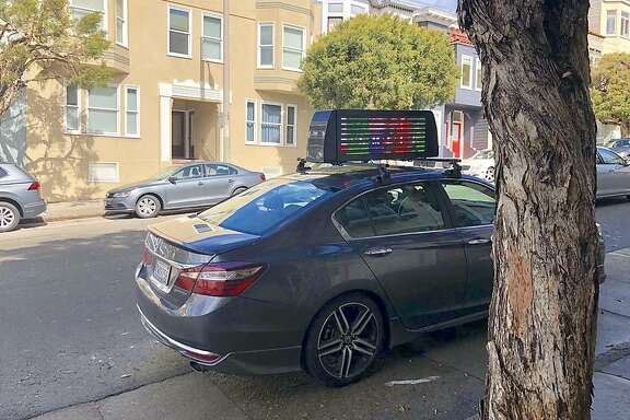 A passerby took this image of a car with both Uber and Lyft stickers and a rooftop video screen in San Francisco's Russian Hill in March.