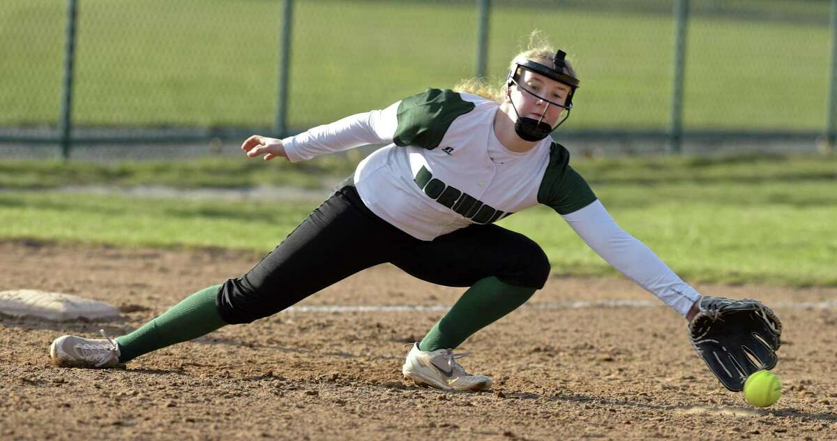 Norwalk's Catherine Sheehan stretches to try to grab a hard-hit ground ball in Thursday's game against Newtown.