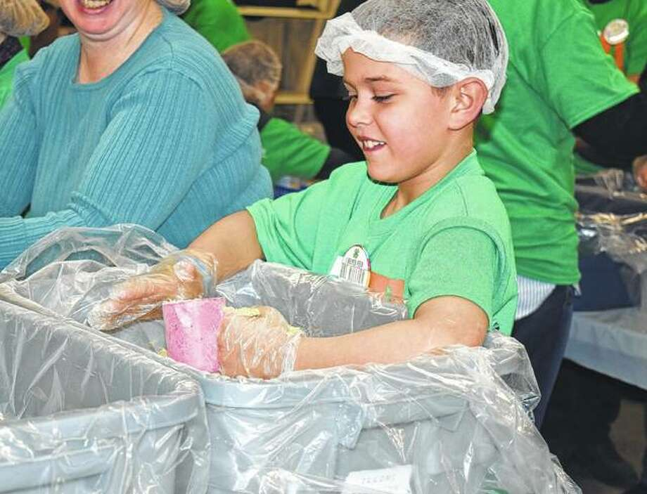 Ben Kvorka, 8, measures rice to be added to a meal that will be going to a family in need. Kvorka, along with other members of 4-H and volunteers, prepared the food packages to help Illinois 4-H reach the 1 million mark of meals packaged by 4-H groups across the state since 2013. Photo: Samantha McDaniel-Ogletree | Journal-Courier