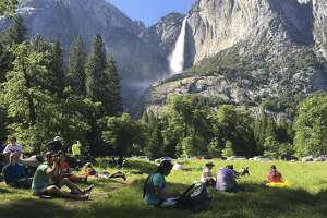 File - In this May 25, 2017 file photo, a class of eighth grade students and their chaperones sit in a meadow at Yosemite National Park, Calif., below Yosemite Falls. Yosemite National Park officials are canceling camping reservations this weekend because of a major storm expected to hit Northern California. Park officials say the warm Pacific storm is expected to have a significant effect on the park and surrounding areas starting Friday, April 6, 2018. Roadways, campgrounds and other facilities could be affected. (AP Photo/Scott Smith, File)