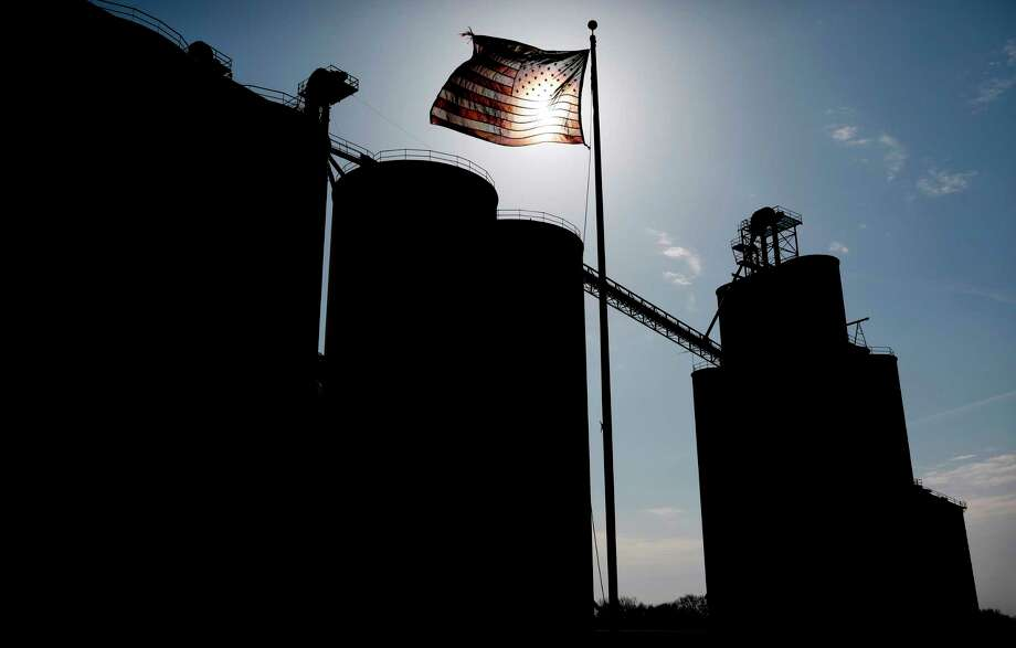 A flag flies over the Heartland Co-op grain elevator, Thursday, April 5, 2018, in Dallas Center, Iowa. The trade dispute with China is threatening to rattle small-town economies and election-year politics. Just seven months before the 2018 midterm elections, Trump's faceoff with China over trade has exposed an unexpected political vulnerability in what was supposed to be the Republican Party's strongest region: rural America. (AP Photo/Charlie Neibergall) Photo: Charlie Neibergall / Copyright 2018 The Associated Press. All rights reserved.