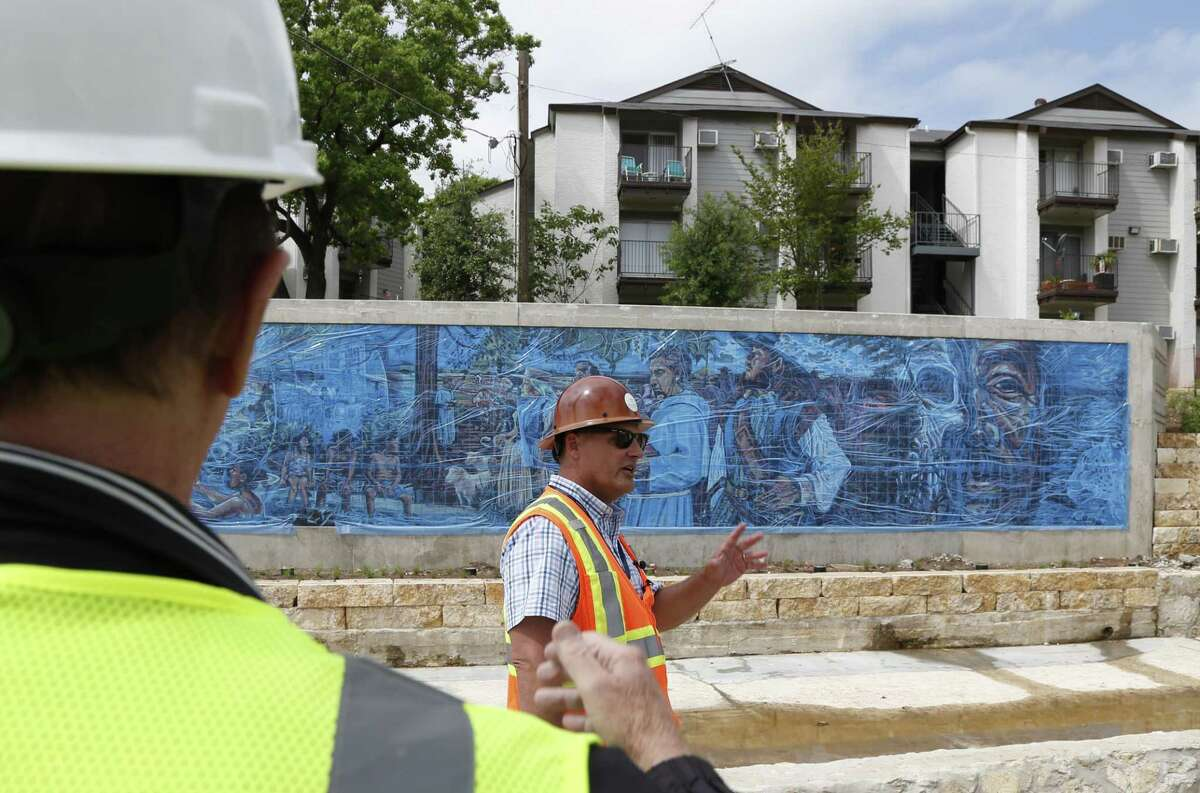 Kerry Averyt, a senior engineer with the San Antonio River Authority, and Bexar County Judge Nelson Wolff (left) toured the construction site of the San Pedro Creek Culture Park about a month before the first phase of the venue opened downtown. The Soap Factory Apartments, previously known as Soapworks and Towne Center, are shown in the background.