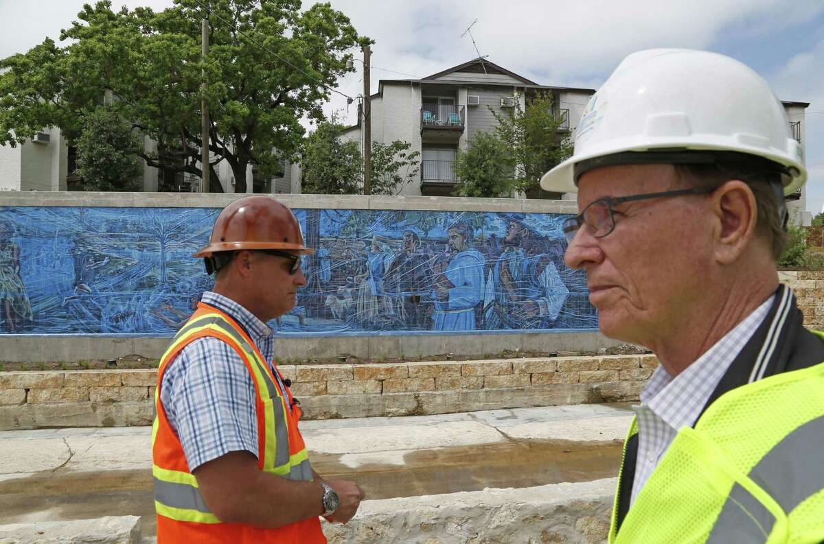 Kerry Averyt, a senior engineer with the San Antonio River Authority, and Bexar County Judge Nelson Wolff (right) toured the first phase of the San Pedro Creek Culture Park about a month before it opened. Averyt is project manager of the San Pedro Creek renovations. The Soap Factory Apartments are shown in the background.