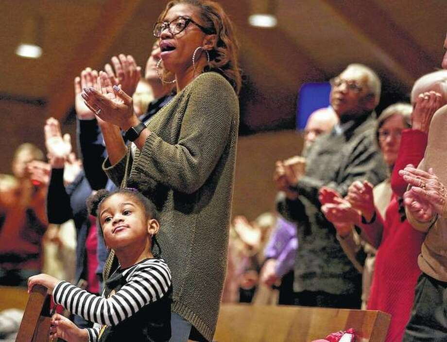 Lincon Reed, 4, of Evergreen Park and her mother, Antoniya, delight to the sounds of a choir during a Martin Luther King Jr. Remembrance Service at Our Saviour's Lutheran Church in Arlington Heights on Wednesday. April 4 marked the day 50 years ago that King was assassinated.