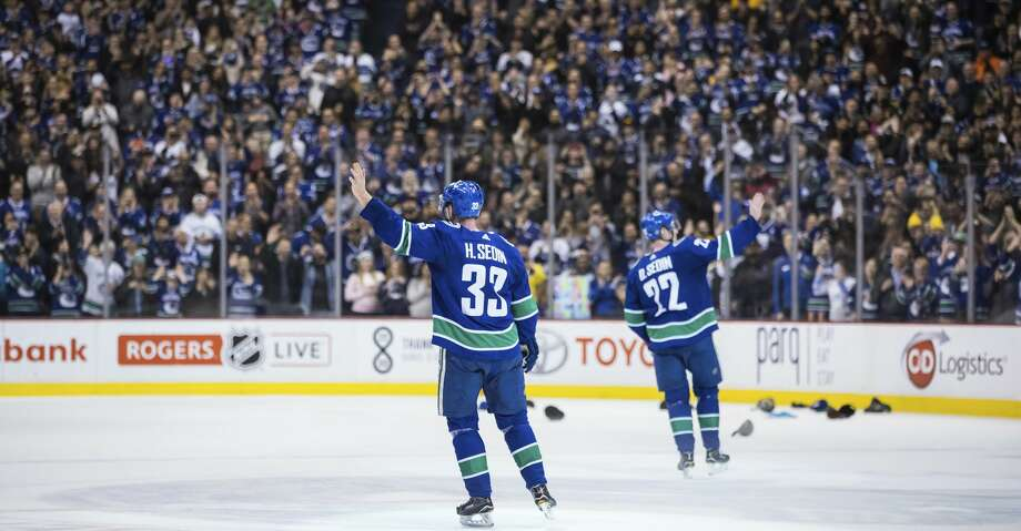 Vancouver Canucks' Henrik Sedin, left, and his twin brother, Daniel Sedin, wave to the crowd after the Canucks defeated the Arizona Coyotes 4-3 in the brothers' last home NHL hockey game, Thursday, April 5, 2018, in Vancouver, British Columbia. (Darryl Dyck/The Canadian Press via AP) Photo: DARRYL DYCK/Associated Press