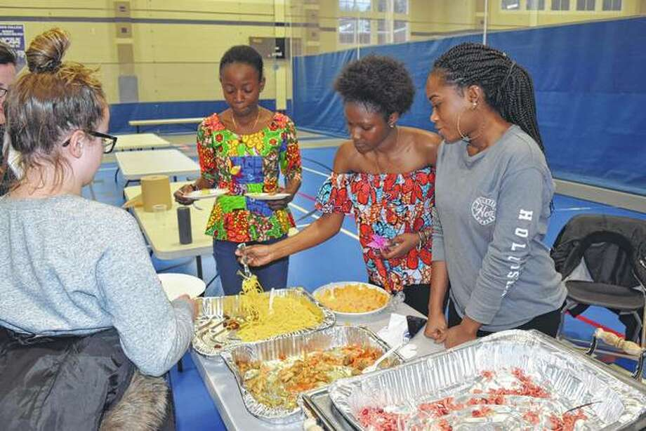 An unidentified young woman (left) is served some food native to Ghana by IC students Akua Biaa Adu (second from left), Hateeya Salifu and Rachel Sefah, all from Ghana, Thursday at Illinois College's Multicultural Festival in IC's Bruner Fitness and Recreation Center. Photo: Greg Olson | Journal-Courier