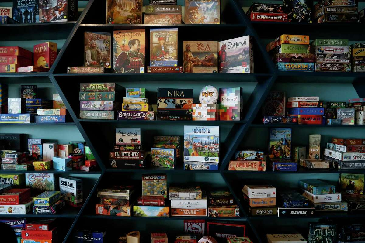 Shelves full of board games on a wall at Tea + Victory, a board game cafe opening April 10 at 2030 E. TC Jester.