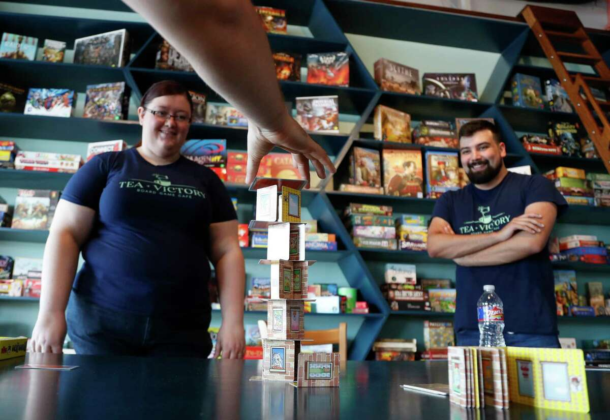 """""""Game Guides"""" Ryan Escontrias and Rachel Rentz play Rhino Hero at the Houston board game cafe, Tea + Victory, 2030 E. TC Jester. The cafe is stocked with more than 500 board games and Game Guides, who are game experts there to help customers select and play games."""