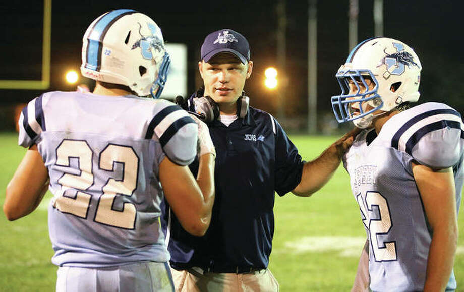 Jersey's coach Jon Adkins (middle) speaks with Logan Chandler (left) and Connor Norris during Mississippi Valley Conference football game at Snyders Sports Complex in Jerseyville during his first season as coach in 2016. On Friday, Adkins announced on Twitter that he was taking a job in Florida. Photo: Billy Hurst / For The Telegraph