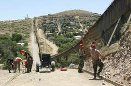 FILE - In this June 20, 2008, file photo, members of the 200th Red Horse Air National Guard Civil Engineering Squadron from Camp Perry in Ohio, including Tech Sgt. David Hughes, right, and Tech Sgt. William Bunker, second from right, work on building a road at the border in Nogales, Ariz. National guard contingents in U.S. states that border Mexico say they are waiting for guidance from Washington to determine what they will do following President Donald Trump's proclamation directing deployment to fight illegal immigration and drug smuggling. Governors of the border states of Arizona and New Mexico have welcomed deployment of the Guard along the southwest border as a matter of public safety.  (AP Photo/Ross D. Franklin, file)