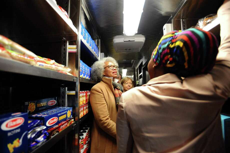 New Neighborhoods director Sonya Van Norden, center, listens to case worker Kislene Bosse Belizaire give a tour of the fully stocked Person to Person Mobile Food Pantry during the launch party on Fairfield Ave. in Stamford, Conn. on Thursday, April 5, 2018. Photo: Michael Cummo / Hearst Connecticut Media / Stamford Advocate