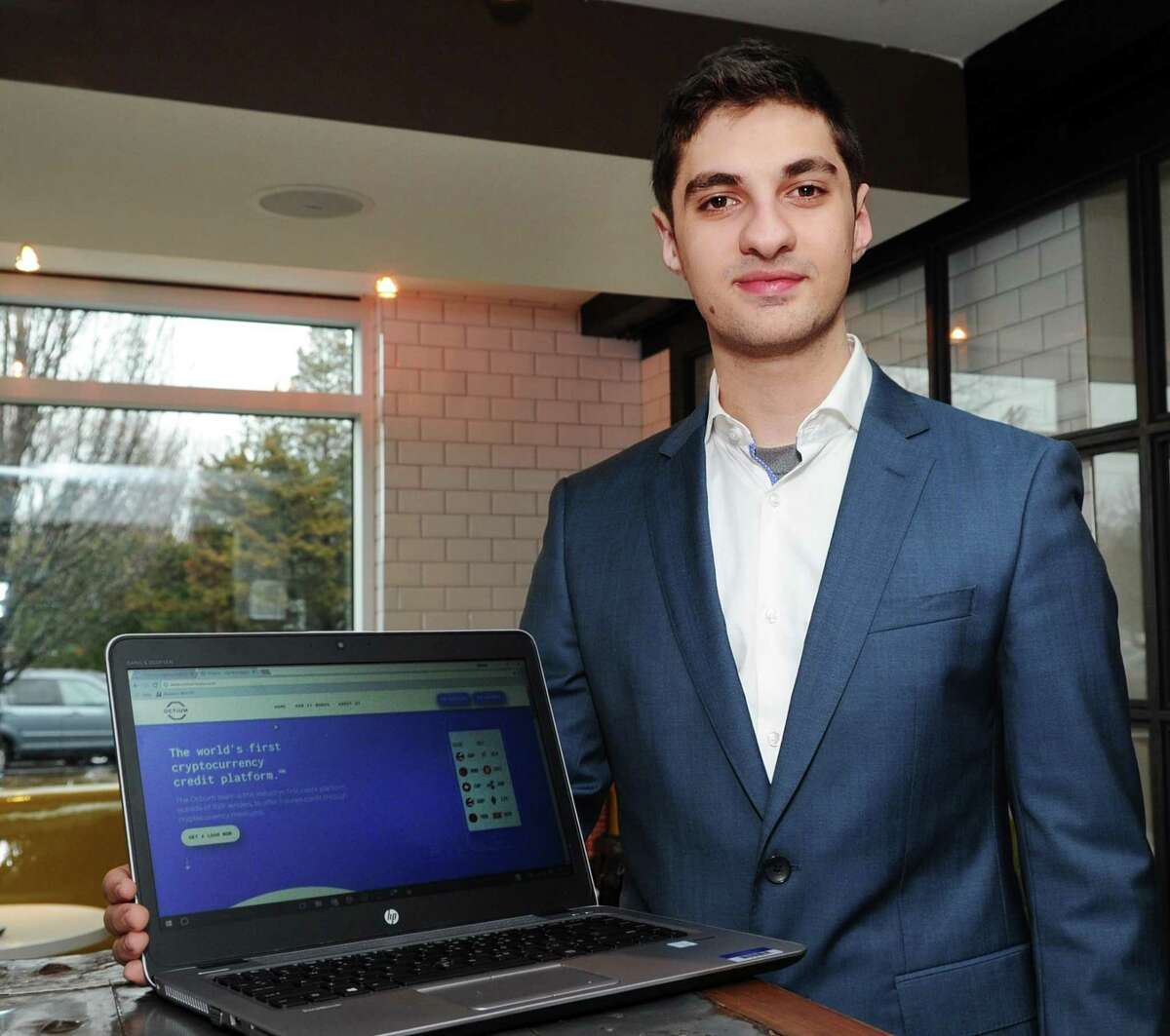 Marc Baghadjian with a computer showing the website of his company, Octium. Baghadjian, a 2017 graduate of the Brunswick School, is an entrepreneur.
