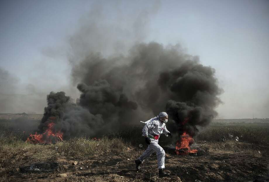 A Palestinian protester runs out of the smoke of burning tires during a protest at the Gaza Strip border. Photo: Khalil Hamra / Associated Press
