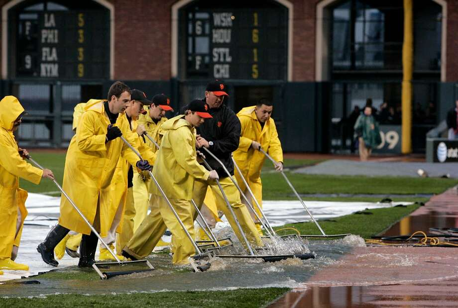FILE-- Groundskeepers remove rain water from the field and tarp during a rain delay on April 7, 2006. That game against the Dodgers was played. Two more games against the Astros during that homestand were rained out. Photo: PAUL CHINN / SFC