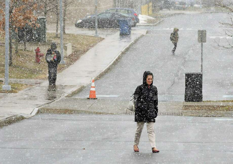 Snow falls as people walk about at Hudson Valley Community College on Friday, April 6, 2018 in Troy, N.Y. (Lori Van Buren/Times Union) Photo: Lori Van Buren, Albany Times Union