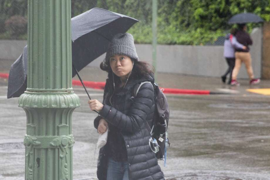 A pedestrian in downtown Oakland crosses the street during a rainstorm that hit the Bay Area on Friday April 6, 2018. Photo: SF Gate / Douglas Zimmerman