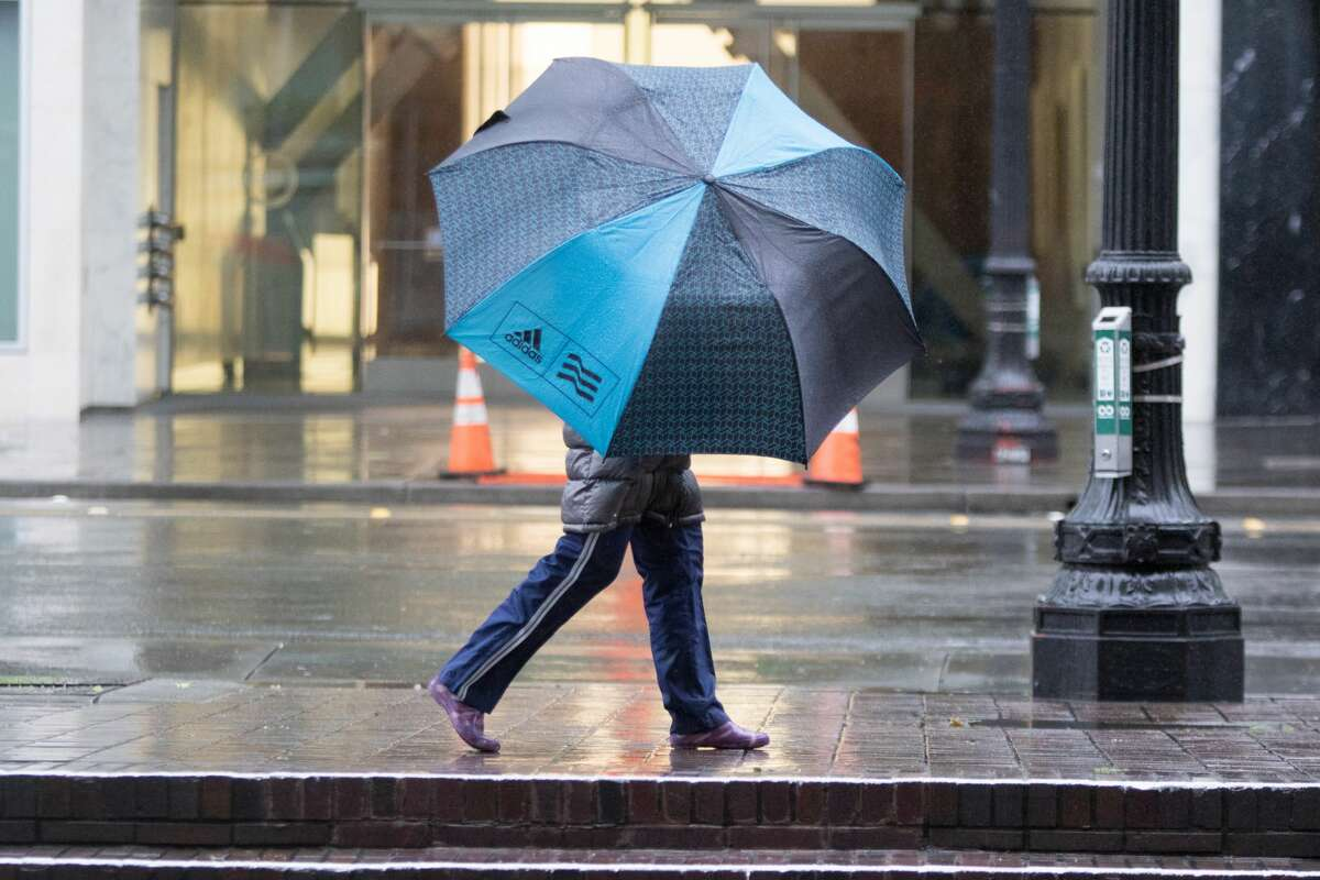 A pedestrian in downtown Oakland uses an umbrella during the rainstorm that hit the Bay Area on Friday April 6, 2018.