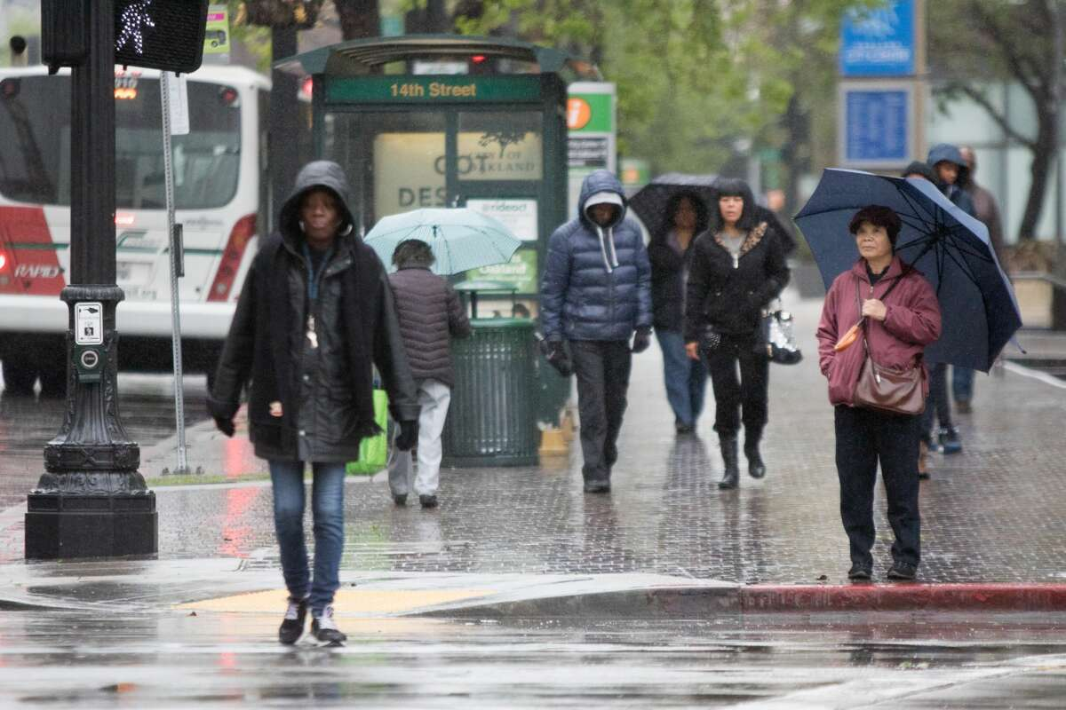 Pedestrians in downtown Oakland make their way during the rainstorm that hit the Bay Area on Friday April 6, 2018.
