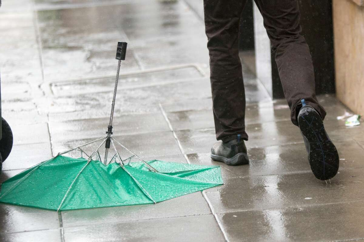 A pedestrians walks past a broken umbrella in downtown Oakland during the rainstorm that hit the Bay Area on Friday April 6, 2018.