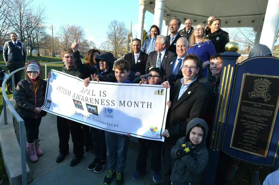 "Family friends and city leaders join organizer Jeff Spahr on the steps of the gazebo on the Norwalk Green on Thursday to proclaim April as Autism Awareness Month and light the gazebo in blue for the worldwide ""Light It Up Blue"" campaign. Photo: Alex Von Kleydorff / Hearst Connecticut Media / Norwalk Hour"