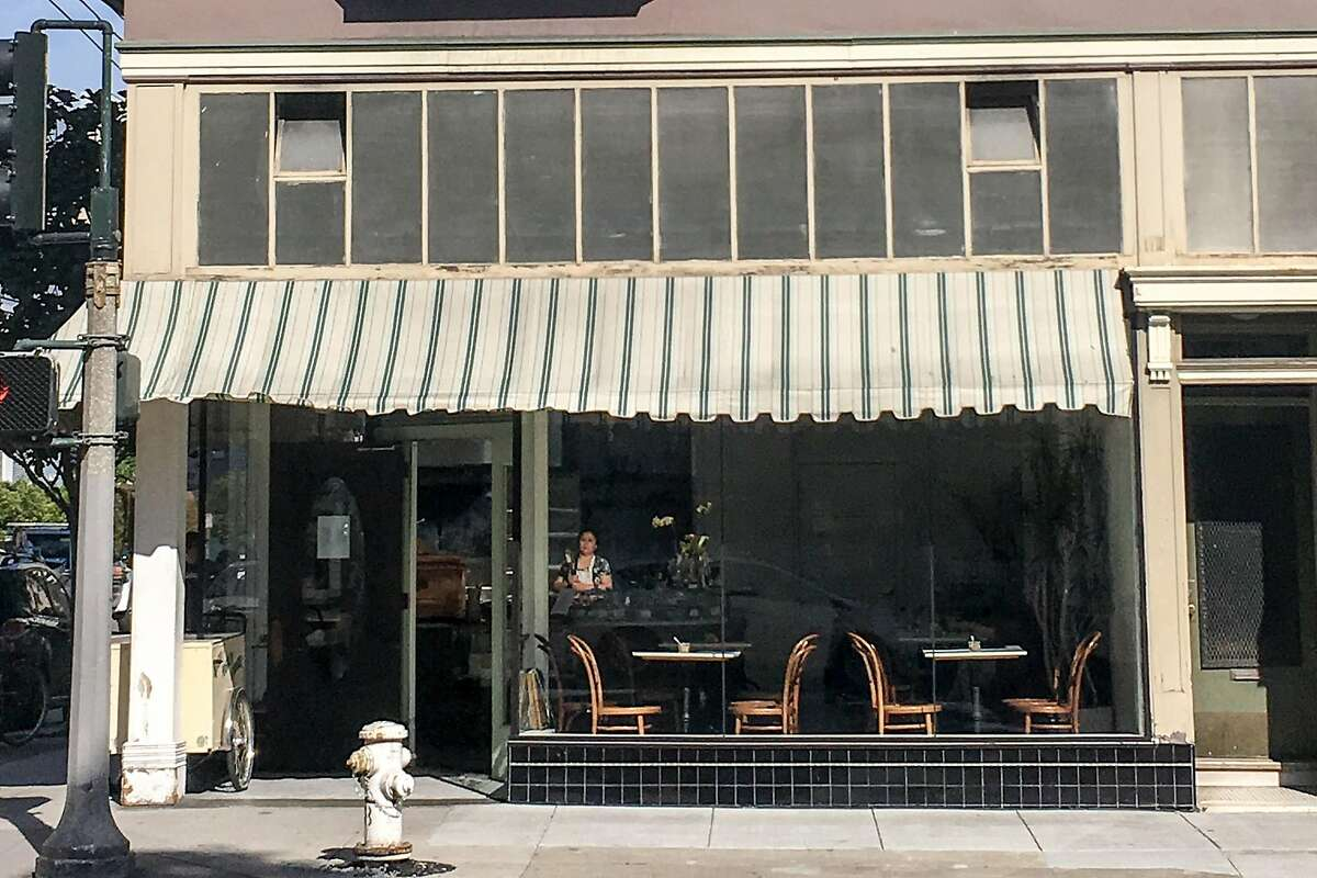 The exterior of 20th Century Cafe in April 2018, with recently repaired windows.