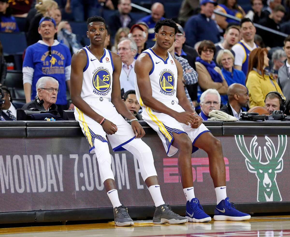 Golden State Warriors' Chris Boucher and Damian Jones wait to enter the game in 4th quarter during Warriors' 117-106 win over Los Angeles Lakers in NBA game at Oracle Arena in Oakland, Calif., on Wednesday, March 14, 2018.