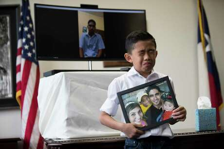 Walter Escobar, 8, becomes emotional as he holds a photo of his family and his father Jose Escobar live on video chat  on the background during a press conference on which Congressman Al Green (TX-09) announces a plan to introduce The Reentry and Reunification Act of 2018, Friday, April 6, 2018, in Houston.