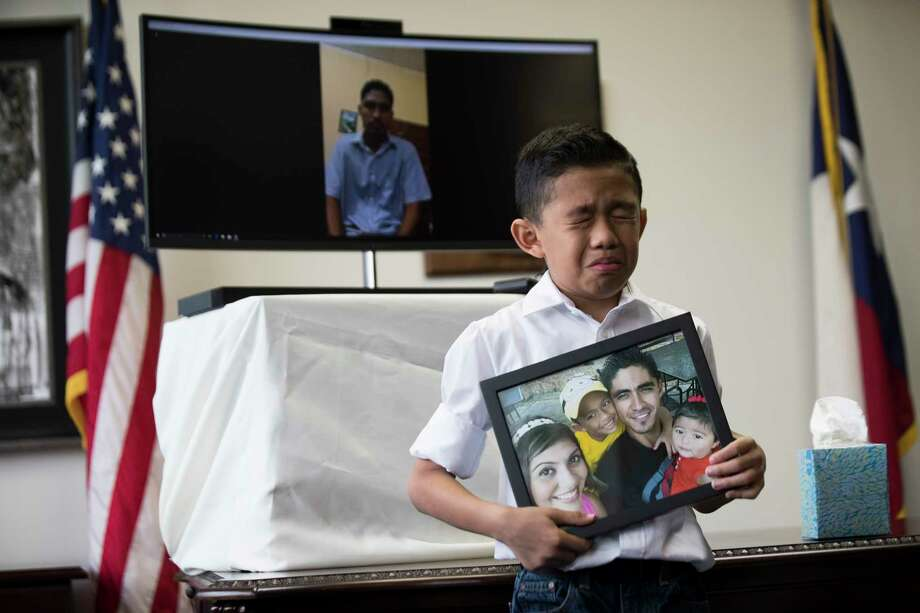 Walter Escobar, 8, becomes emotional as he holds a photo of his family and his father Jose Escobar live on video chat  on the background during a press conference on which Congressman Al Green (TX-09) announces a plan to introduce The Reentry and Reunification Act of 2018, Friday, April 6, 2018, in Houston. Photo: Marie D. De Jesus, Houston Chronicle / © 2018 Houston Chronicle