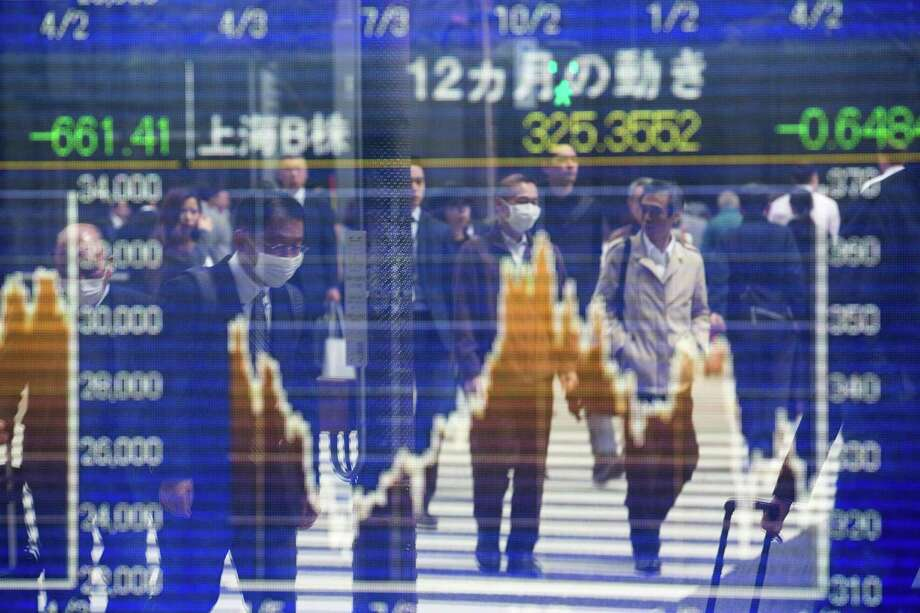 Pedestrians are reflected on a stock indicator showing share prices of the Shanghai B-share stock price in Tokyo on April 5, 2018. Tokyo stocks closed higher on April 5 as fears of a US-China trade war eased and the yen weakened against the dollar. Photo: BEHROUZ MEHRI, Contributor / AFP/Getty Images / AFP or licensors